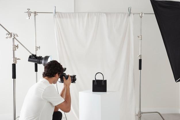Jovem trabalhando em seu estúdio fotográfico