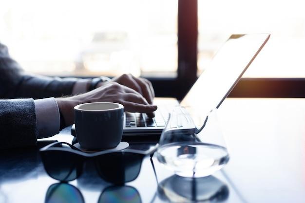 Jovem trabalhando em seu laptop em uma cafeteria