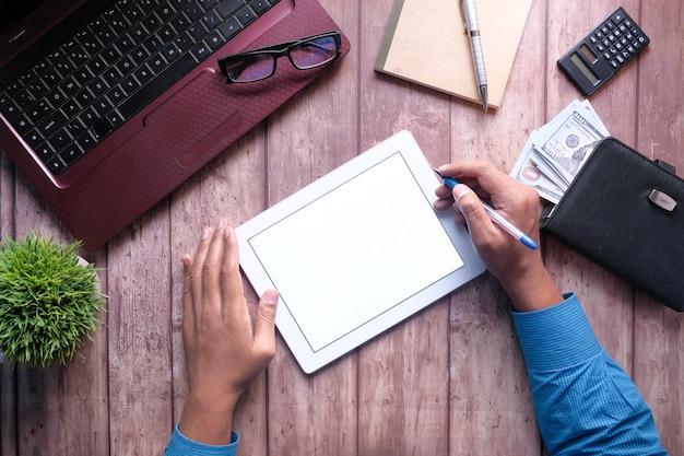 Jovem trabalhando em tablet digital com laptop e bloco de notas na mesa