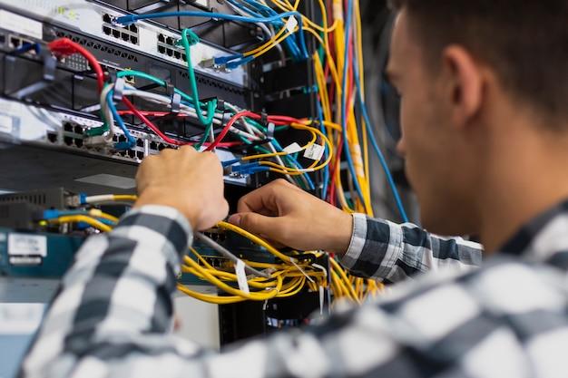 Jovem trabalhando em um interruptor ethernet closeup