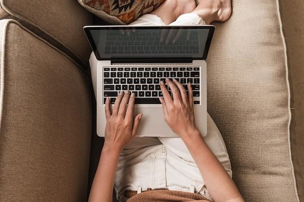 Jovem trabalhando em um laptop deitada no sofá