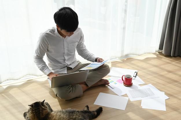 Jovem trabalhando em um laptop e sentado no chão da sala de estar.