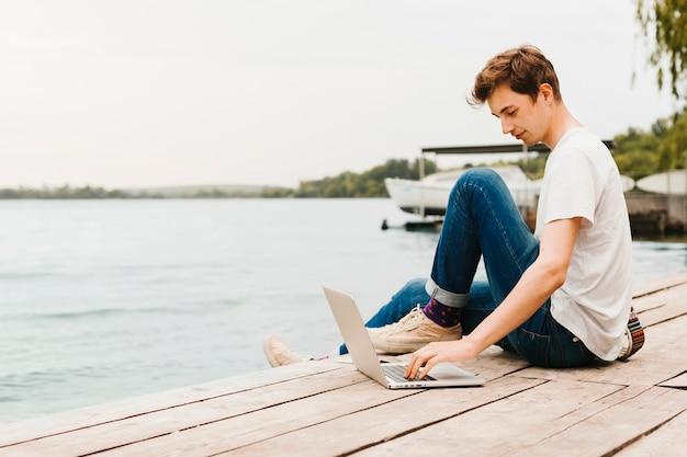 Jovem trabalhando no laptop à beira do lago