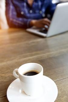 Jovem trabalhando no laptop com café na mesa
