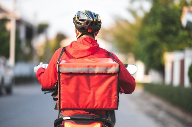 Jovem trabalhando para um serviço de entrega de comida, verificando uma motocicleta de estrada na cidade