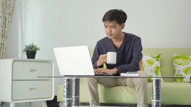 Jovem trabalhando seriamente em casa usando um laptop com um copo de bebida