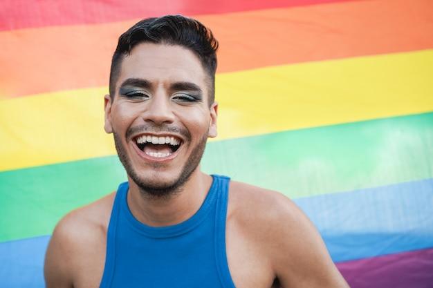 Jovem transexual com maquiagem sorrindo para a câmera com a bandeira do arco-íris lgbt no fundo - foco no rosto