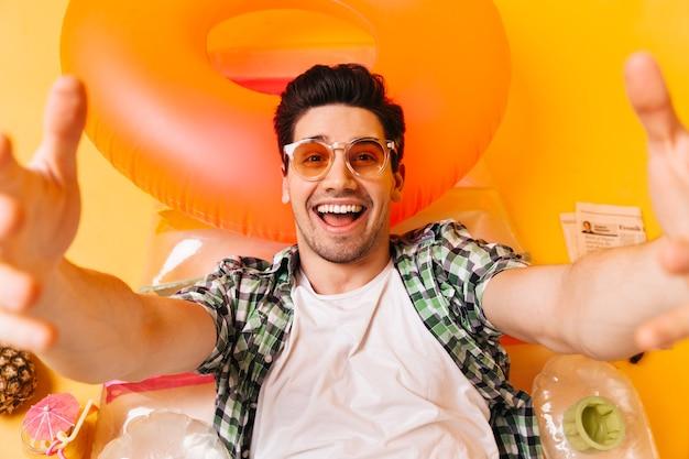 Jovem travesso em camisa xadrez e óculos laranja sorri e tira selfie no colchão inflável.