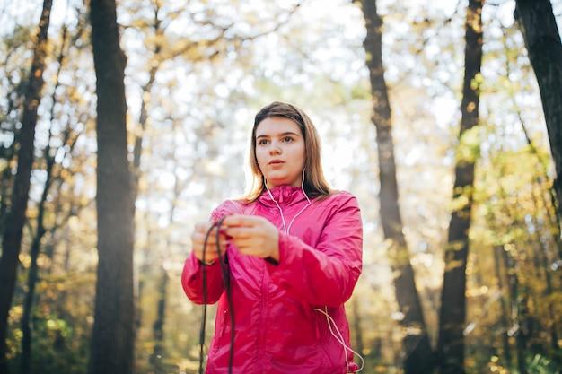 Jovem treina e ouve música ao ar livre e pula em uma corda
