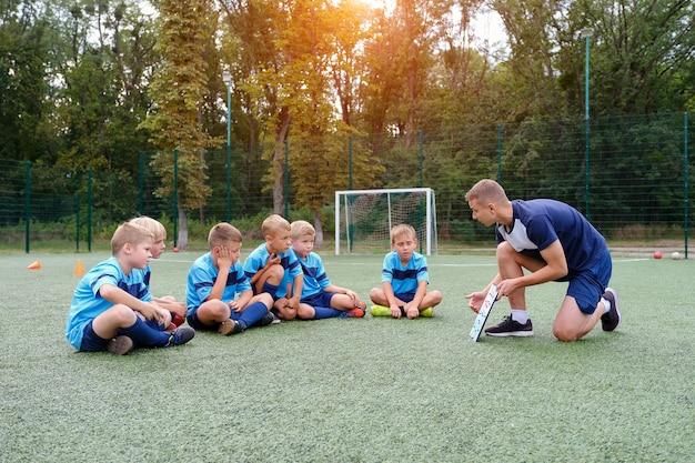 Jovem treinador com prancheta ensina estratégia a crianças jogando no campo de futebol.