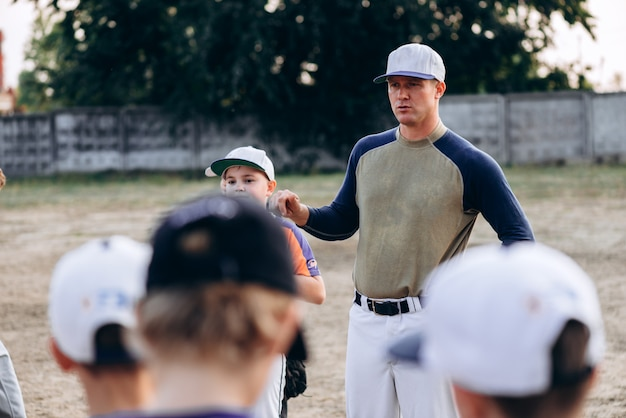 Jovem treinador de beisebol instrui seus alunos antes do jogo