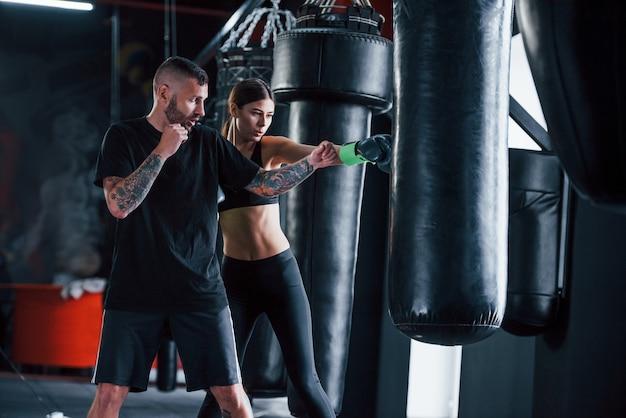 Jovem treinador de boxe tatuado ensina jovem no ginásio.