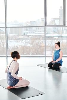 Jovem treinador e menina deficiente sentados em colchonetes em frente ao outro, instrutor dando instruções sobre exercícios de ioga antes do treino