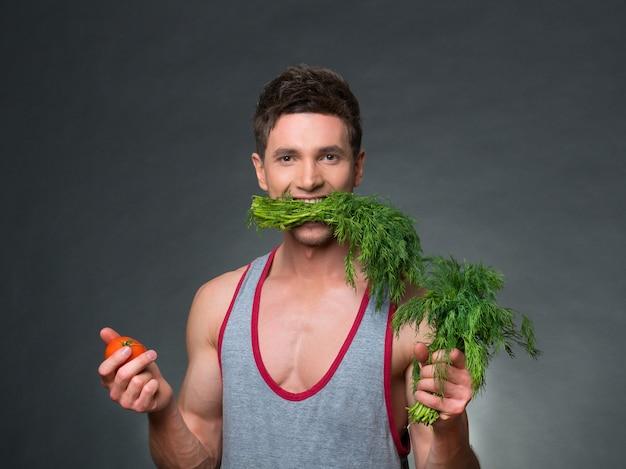 Jovem treinador e nutricionista segurando uma tigela de legumes, sobre fundo preto