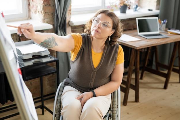 Jovem, treinadora de negócios, mulher, com deficiência, em trajes casuais, sentada em frente ao quadro branco e se preparando para um seminário ou apresentação para designers