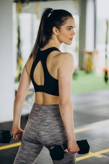 Jovem treinadora se exercitando na academia