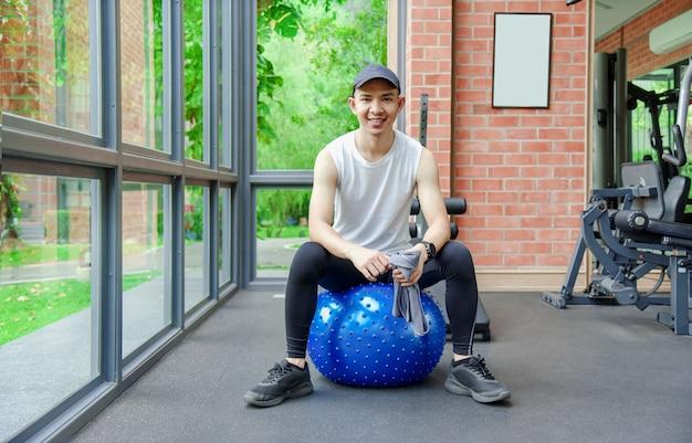 Jovem treinando equilíbrio com bola de ioga na academia de reabilitação esportiva