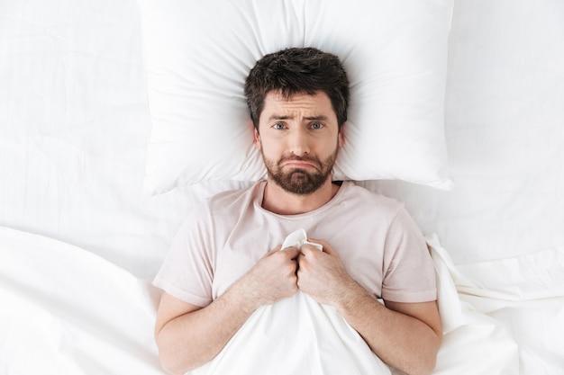 Jovem triste com dor de cabeça de manhã debaixo do cobertor na cama
