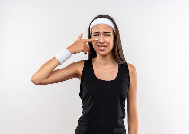 Jovem triste e muito esportiva usando bandana e pulseira apontando para o nariz no espaço em branco