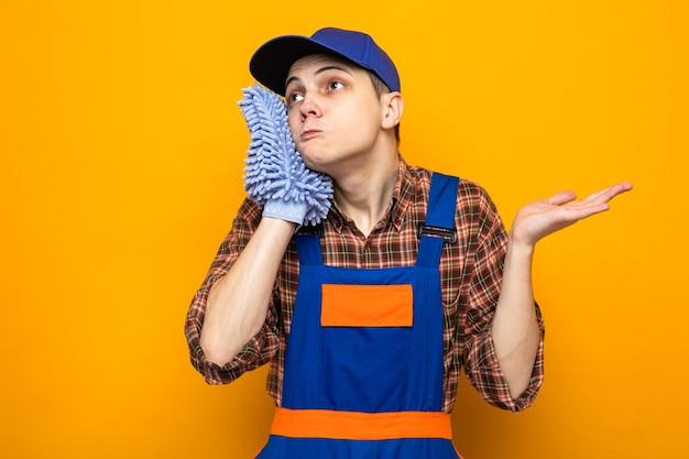 Jovem, triste, espalhando a mão, cara de limpeza vestindo uniforme e boné segurando um pano no rosto