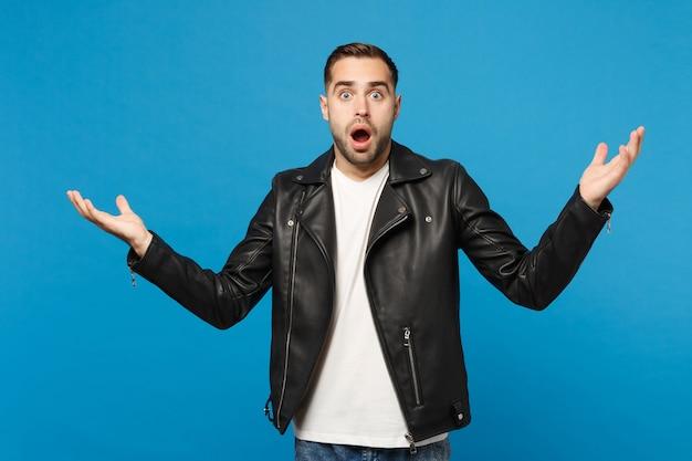 Jovem triste frustrado preocupado com a barba por fazer em camiseta branca de jaqueta preta, olhando a câmera isolada no retrato de estúdio de fundo de parede azul. conceito de estilo de vida de emoções sinceras de pessoas. simule o espaço da cópia.