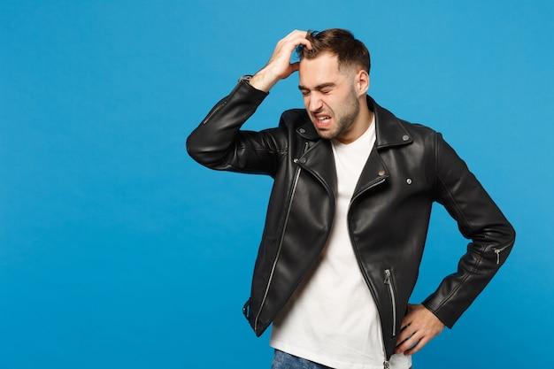 Jovem triste frustrado preocupado com a barba por fazer em uma jaqueta preta de camiseta branca colocou o braço na cabeça isolada no retrato de estúdio de fundo de parede azul. conceito de estilo de vida de emoções sinceras de pessoas. simule o espaço da cópia.