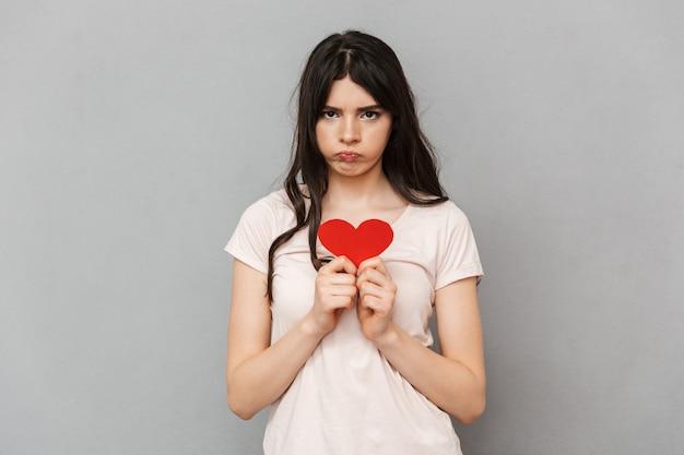 Jovem triste segurando coração isolado