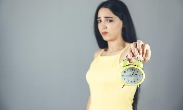 Jovem triste segurando um relógio amarelo
