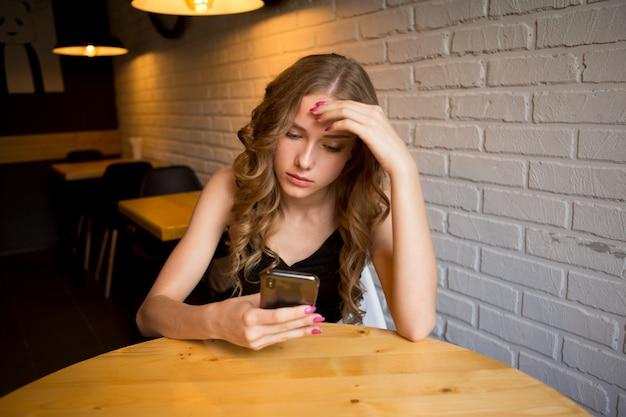 Jovem triste sentada em um café parecendo cansada com o telefone, garota infeliz olhando para o telefone preto,