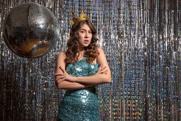 Jovem triste triste e charmosa com vestido azul verde brilhante com lantejoulas e coroa na festa