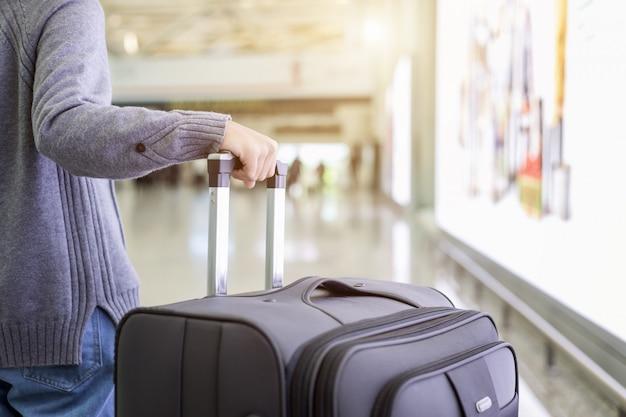 Jovem turista andando e puxa a bagagem no aeroporto