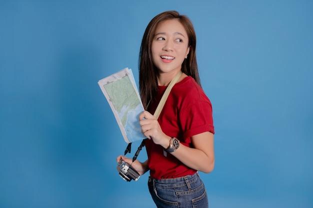 Jovem turista asiática sorrindo e segurando um mapa e uma câmera em azul Foto Premium
