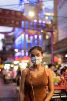 Jovem turista asiática usando máscara para proteção contra surto do vírus corona em chinatown à noite