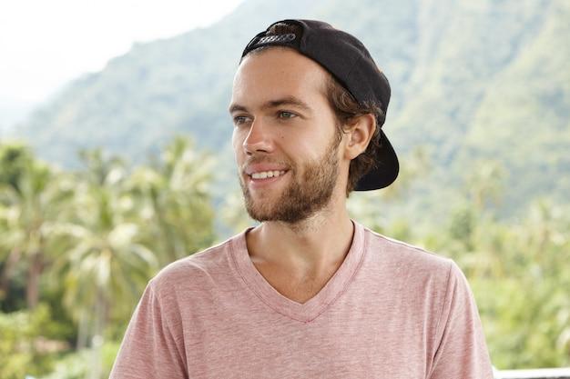 Jovem turista atraente e sorridente de boné preto virado para trás, aproveitando o clima ensolarado e os dias quentes de verão durante as férias em um país tropical