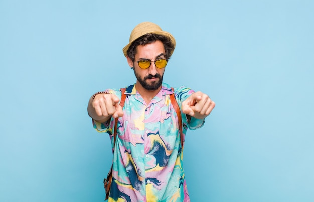 Jovem turista barbudo apontando para a frente com os dois dedos e uma expressão raivosa, dizendo para você cumprir seu dever