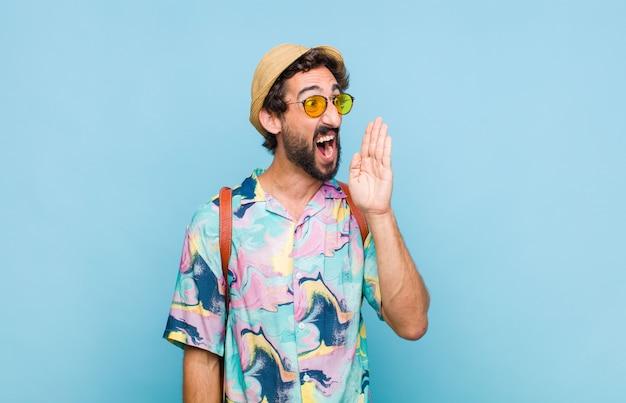 Jovem turista barbudo gritando alto e com raiva para copiar o espaço ao lado, com a mão perto da boca