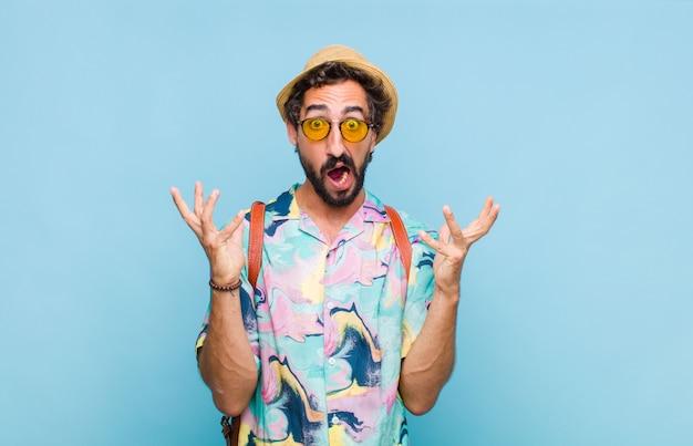 Jovem turista barbudo gritando com as mãos para o alto, sentindo-se furioso, frustrado, estressado e chateado