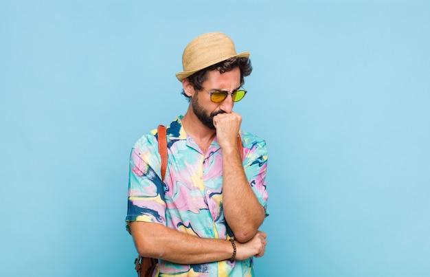 Jovem turista barbudo se sentindo sério, pensativo e preocupado, olhando de lado com a mão pressionada contra o queixo