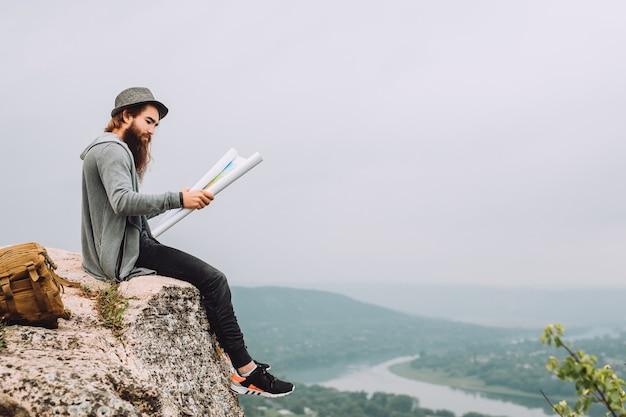 Jovem turista barbudo senta-se em uma rocha alta. e segura o mapa