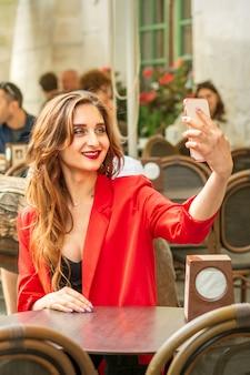Jovem turista caucasiana com uma jaqueta vermelha com mala leva uma selfie à mesa no café ao ar livre.