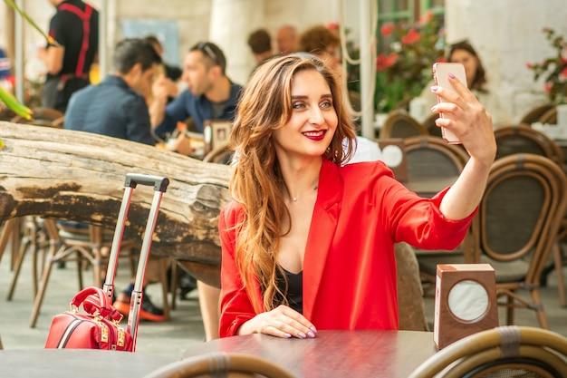 Jovem turista caucasiana com uma jaqueta vermelha com mala leva uma selfie à mesa no café outd.
