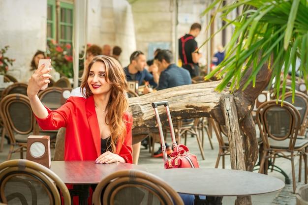Jovem turista caucasiana com uma jaqueta vermelha e uma mala fazendo uma selfie na mesa de um café
