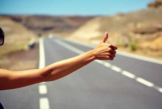 Jovem turista caucasiana pedindo carona ao longo de uma estrada no pôr do sol
