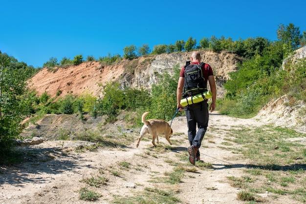 Jovem turista caucasiano explorando lugares lindos com seu cachorro