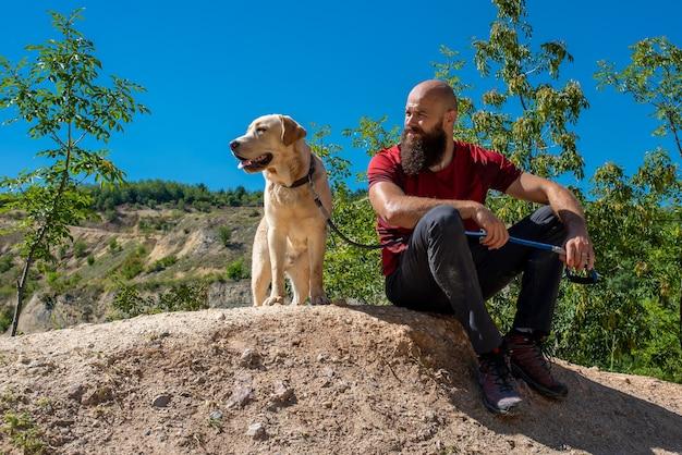 Jovem turista caucasiano explorando lugares lindos com seu labrador retriever