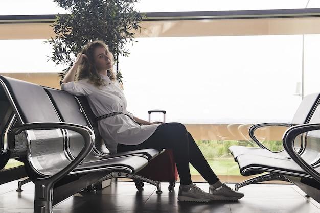 Jovem turista com malas sentada na sala de espera do aeroporto ou da estação ferroviária esperando o voo