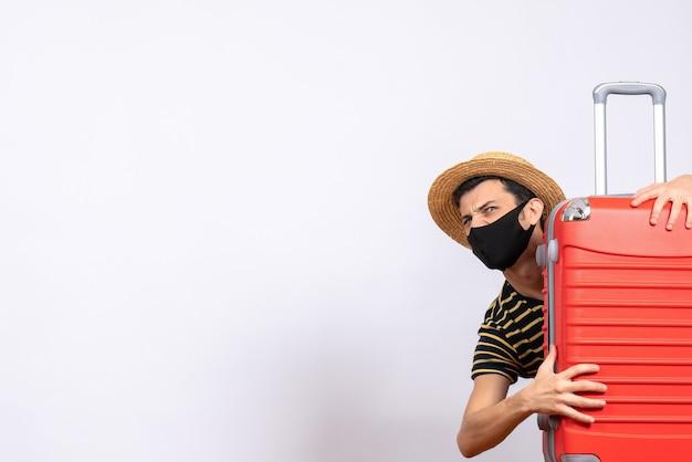 Jovem turista com máscara preta se escondendo atrás de uma mala vermelha