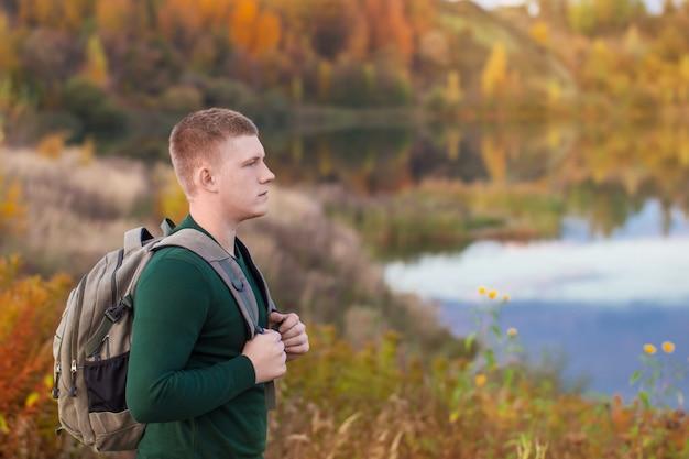 Jovem turista com mochila perto do lago de outono