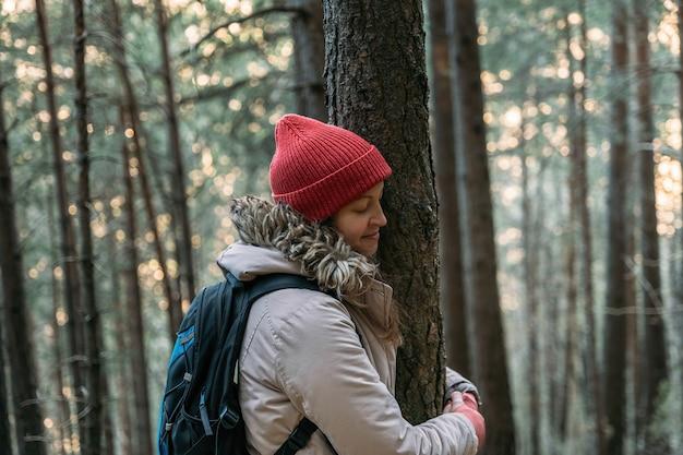 Jovem turista com os olhos fechados e boné vermelho abraçando uma árvore na floresta fria durante a caminhada na montanha, conectando-se à natureza para proteger o conceito de meio ambiente