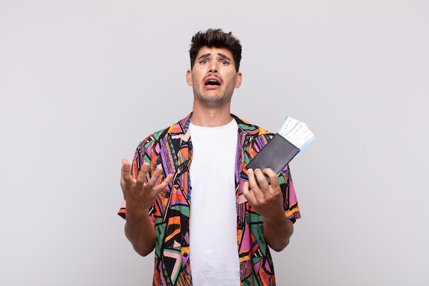 Jovem turista com passaporte parecendo desesperado e frustrado, estressado, infeliz e irritado, gritando e gritando